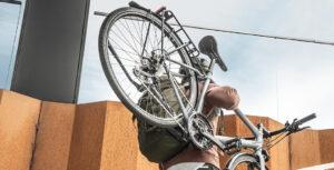 Mann trägt Fahrrad die Treppe hoch - Diamantrad-Blog